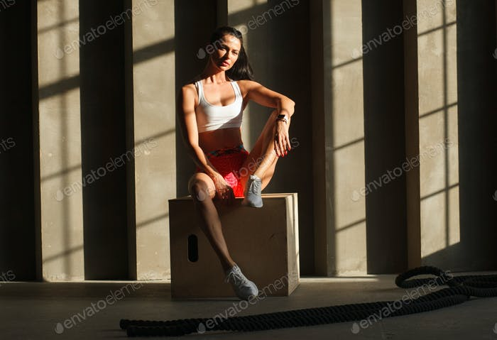 sportswoman sits on crossfit box in gym