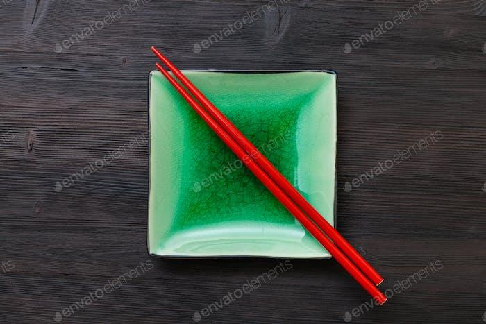 Draufsicht der grünen Untertasse mit Stäbchen auf braun