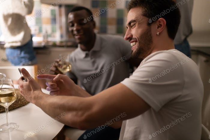 Cheerful guy showing smartphone to black friends