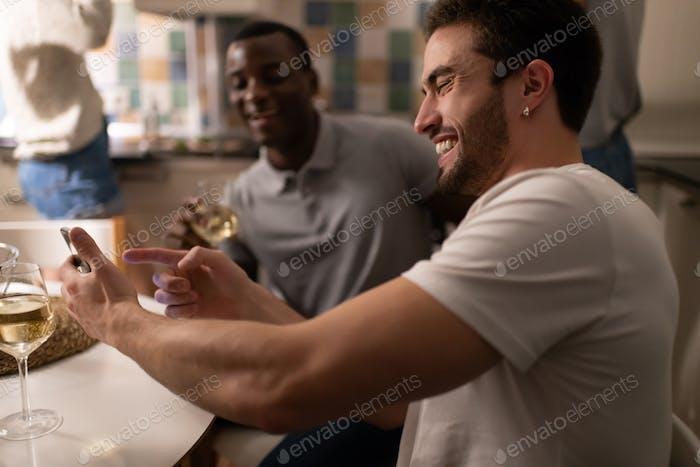 chico alegre mostrando smartphone a negro amigos