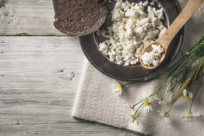 Fresh cottage cheese with bread and flowers on the white wooden table top view