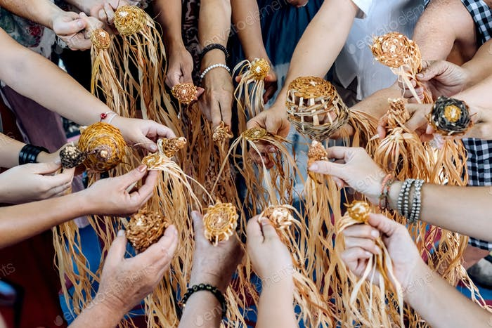 Different ages and nationalities females hands keeping their weaving craft together in a circle.