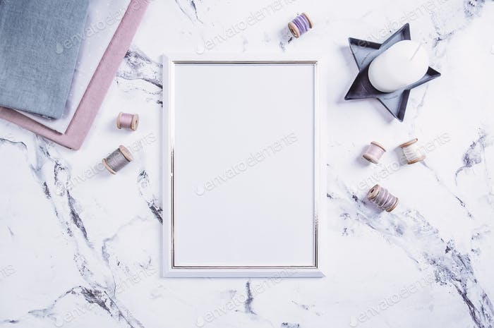 Blank frame and sewing items over marble table