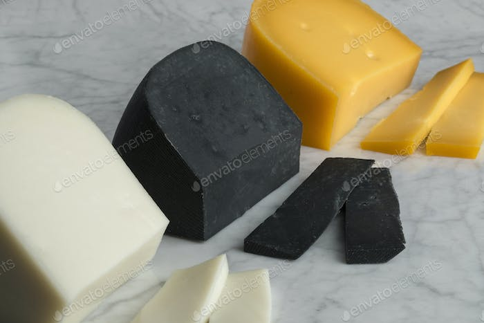 Pieces of white goat cheese, black lemon cheese and Gouda cheese