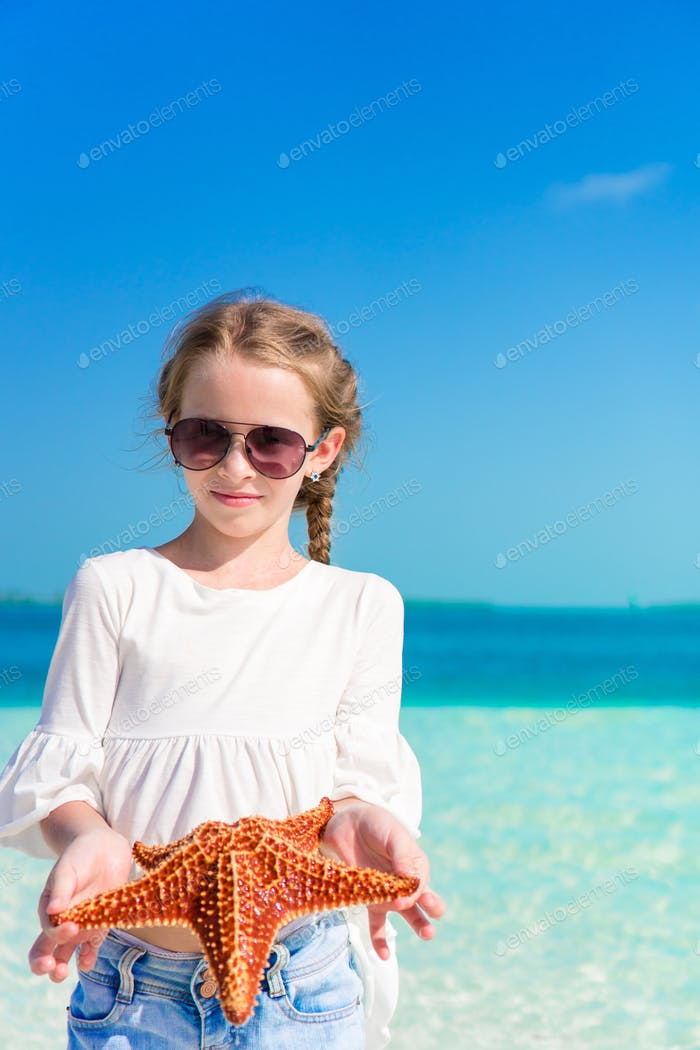Thumbnail for Adorable little girl with starfish on white empty beach