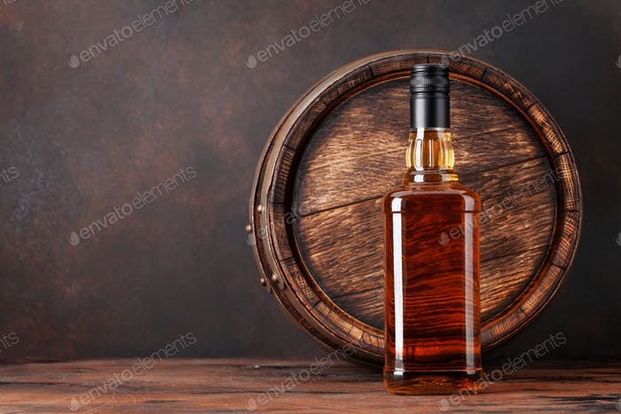 Scotch whiskey bottle and old barrel