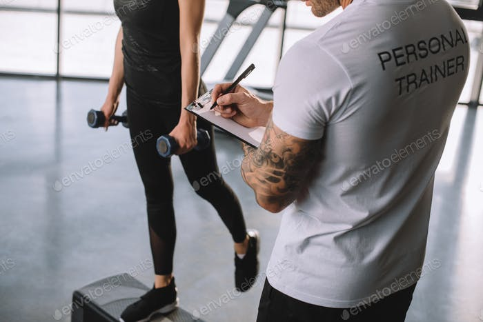 cropped image of male personal trainer writing in clipboard and young sportswoman doing step