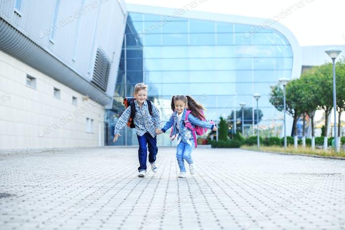 Los niños corren con mochilas. El concepto es volver a la escuela, estudiar, amistad.