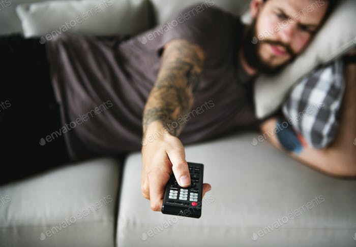 Man lying on a couch watching tv