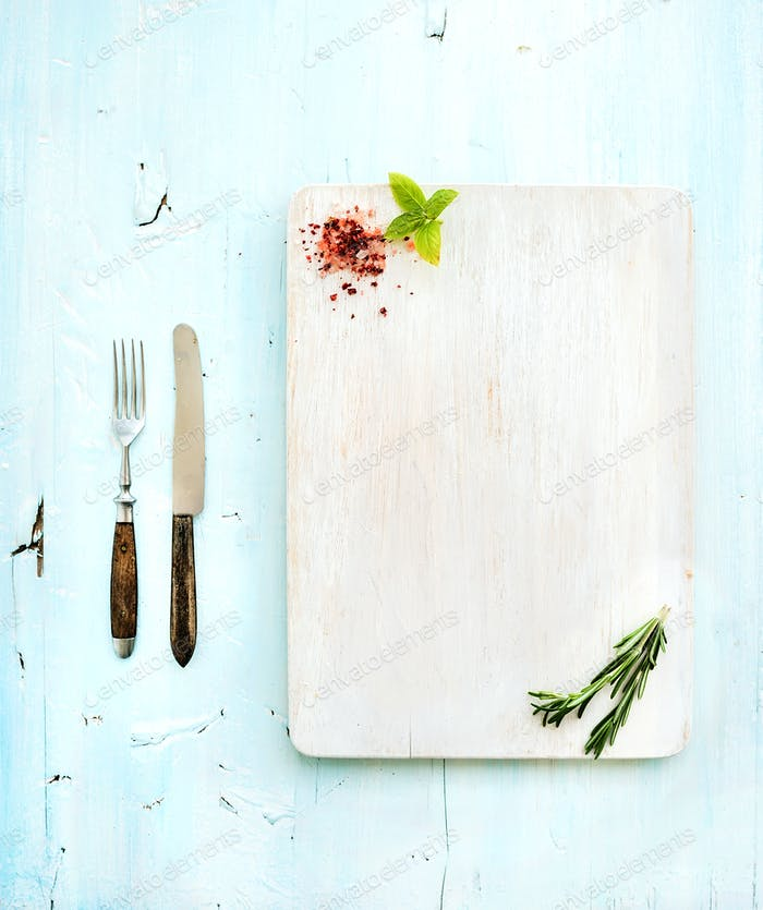 Kitchen-ware set. White wooden chopping board, knife, fork, spices and herbs