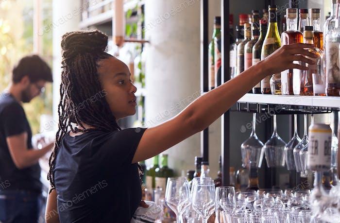 Female Bartender Arranging Bottles Of Alcohol Behind Bar
