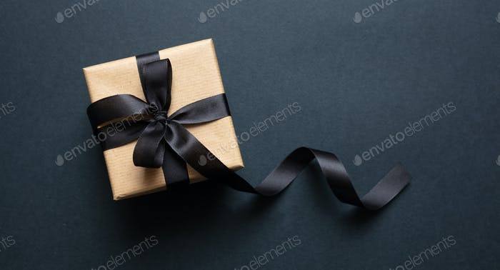 Gift box with black ribbon against black background, Black Friday concept.