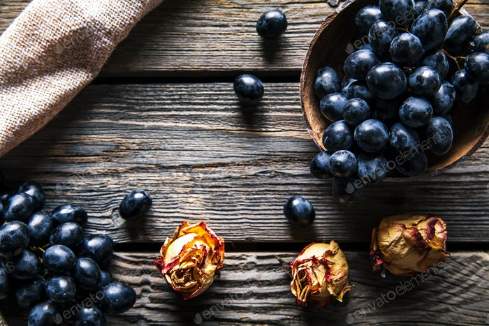 Grapes with dried roses on a wooden background. Fruits, flowers, food