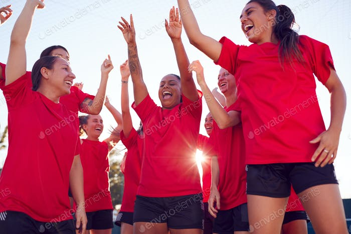 Womens Football Team Celebrating Winning Soccer Match On Outdoor Astro Turf Pitch