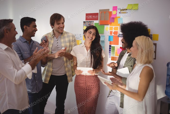 Colleagues applauding for businesswoman in creative office