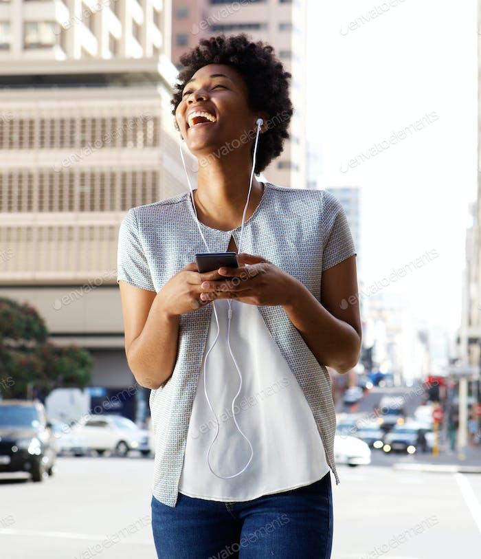 African woman enjoying listening music on her mobile phone