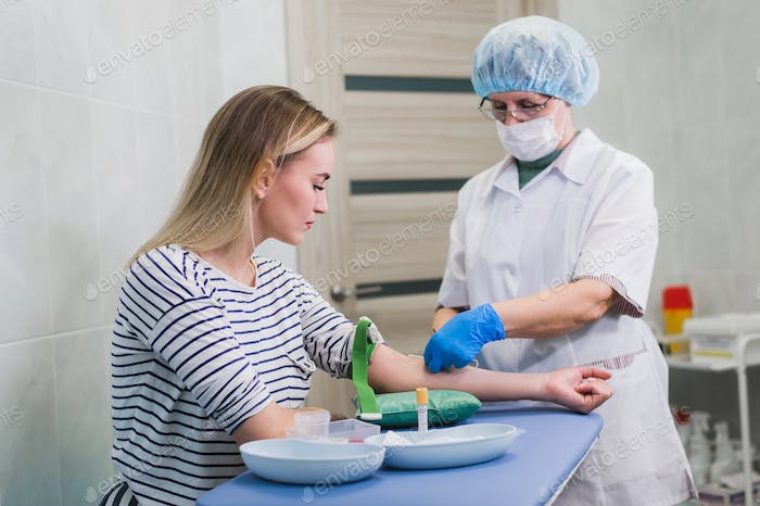 Preparation for blood test with pretty young blond woman by female doctor in white coat medical