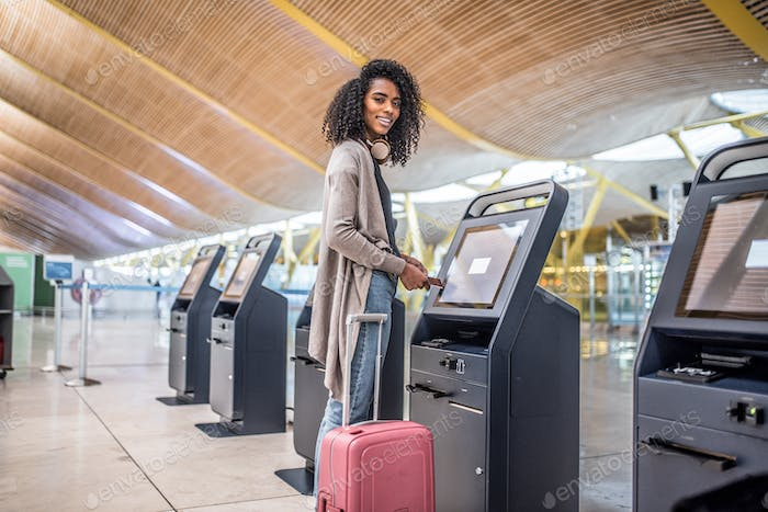 happy woman using the check-in machine at the airport getting th