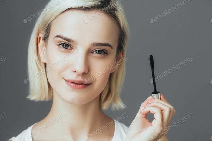 Woman mascara applying brush, female portrait makeup eyelashes.