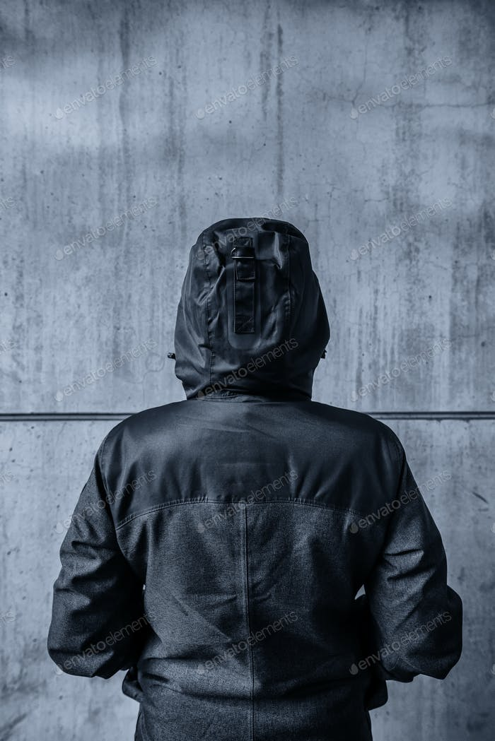 Unrecognizable hooded female person facing concrete wall as insu