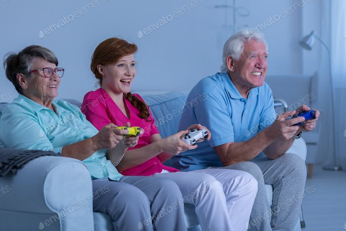 Elderly couple and caregiver playing
