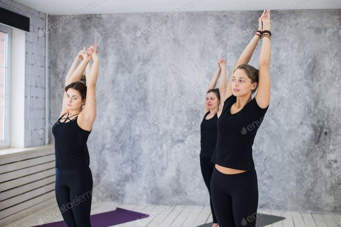 Smiling yogi girl in class in Yoga asana, exercising, stretching