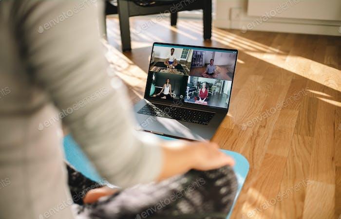 Gruppe von Menschen, die Yoga mit Trainer über Video konferenz praktizieren