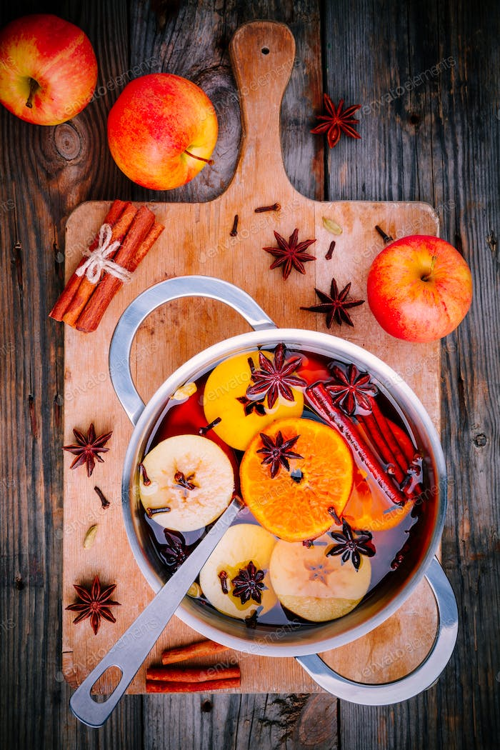 Hot mulled wine drink with citrus, apples, cinnamon sticks, cloves and anise in cooking pan