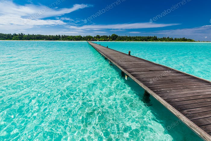Wooden long jetty over lagoon in Maldives with amazing water
