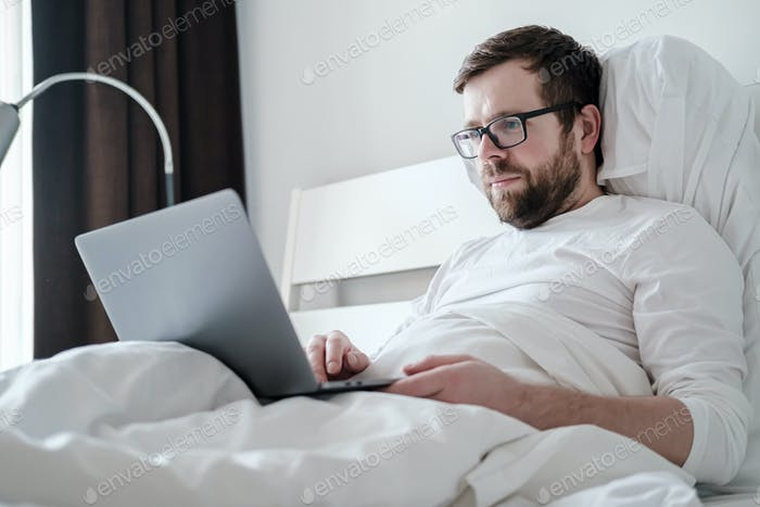 Young freelancer man in pajamas works with a laptop lying in a soft bed