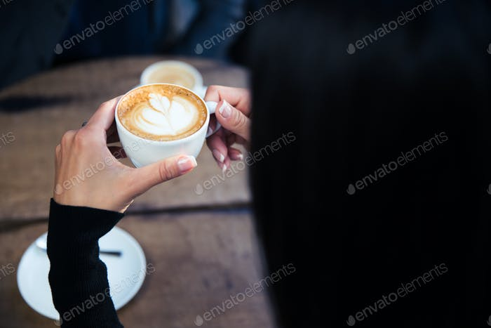 Female hands holding cup with coffee