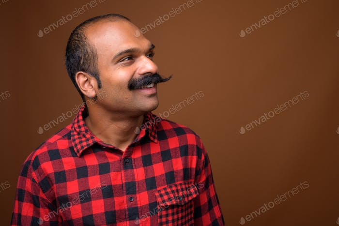 Closeup profile view of happy Indian hipster man with mustache