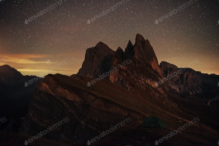 Night photo of Seceda dolomites mountains. Tourists resting in the green tent