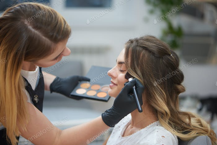 View from side of makeup artist doing visage to woman in beauty salon
