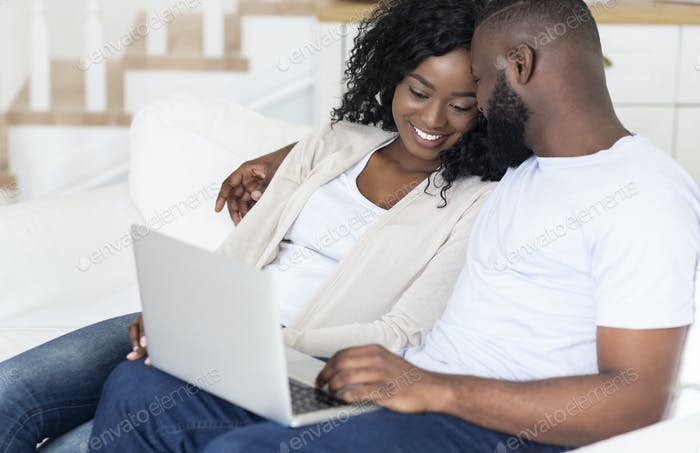 Black couple spending weekend together, watching movie on laptop