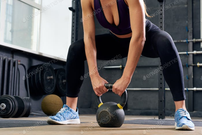 Young Woman Lifting Kettlebell in Squat