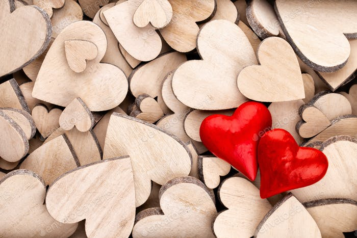 Wooden hearts pattern, one red heart on the wooden heart background.