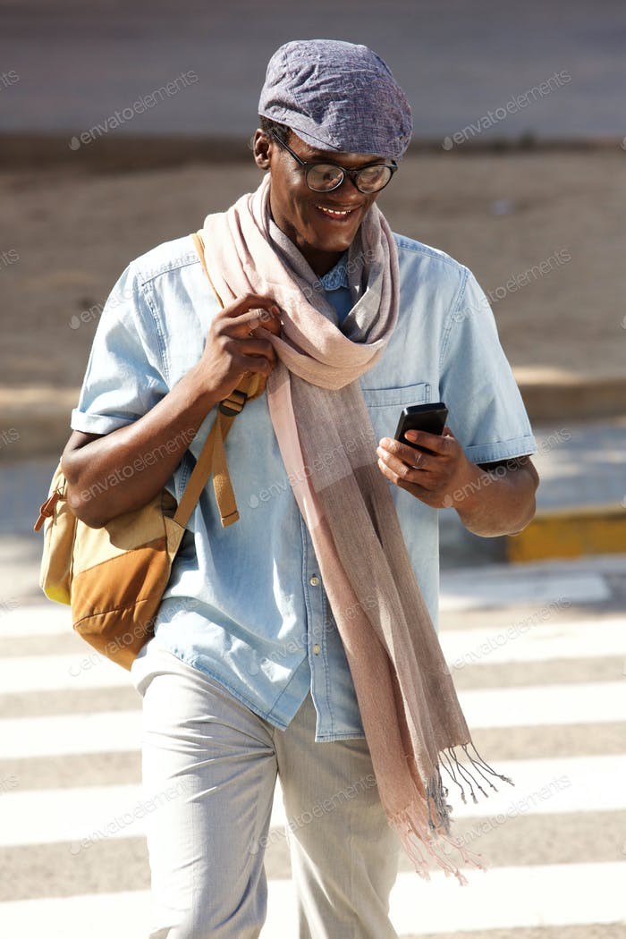 trendy young black guy walking outdoors with cell phone