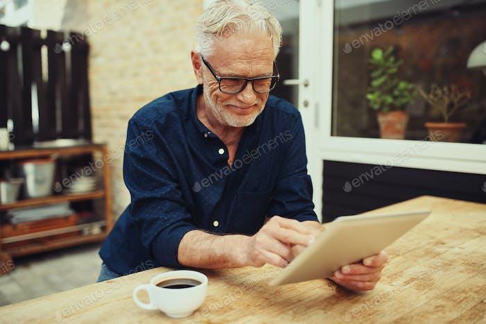 Lächelnd Senior Mann genießen einen Kaffee und mit einer Tablette