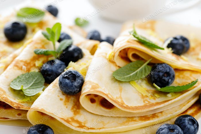 Sweet pancakes wrapped with fresh berries, crepes with blueberry