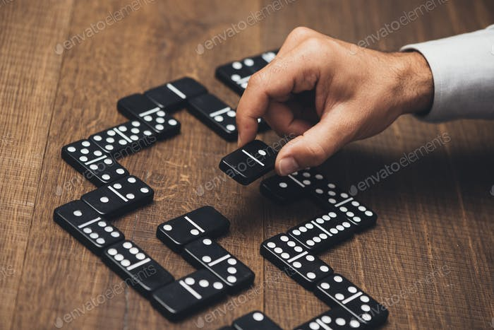 Businessman playing with dominoes