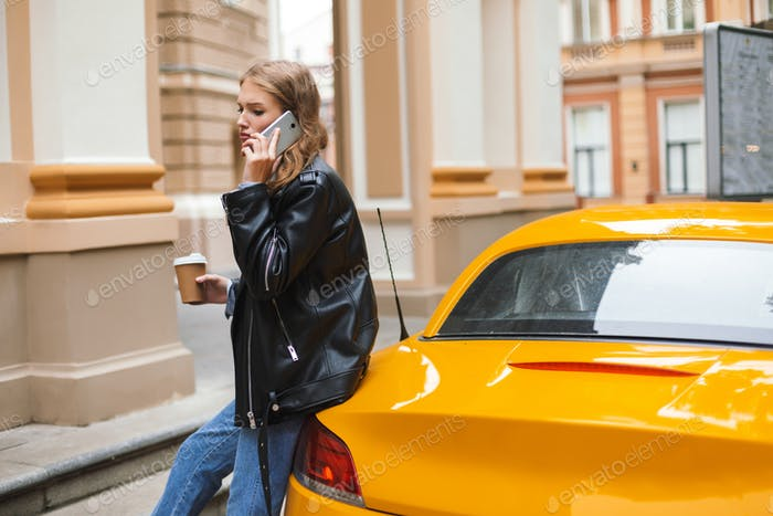 Young upset woman in leather jacket with cup of coffee to go lea