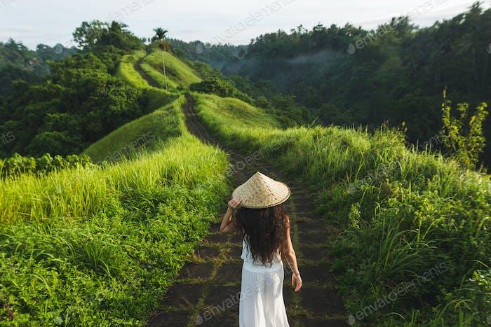 Young beautiful woman walking on Campuhan Ridge way of artists, in Bali, Ubud