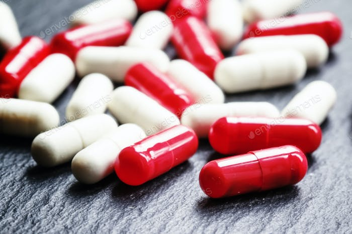 Painkillers pills in red and white capsules