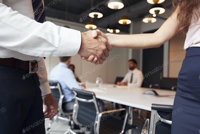 Close Up Of Businessman And Businesswoman Shaking Hands In Modern Boardroom