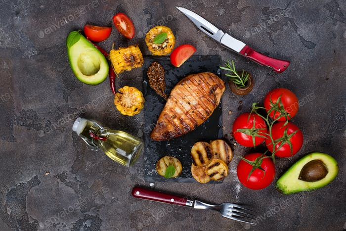 grilled healthy chicken breasts cooked on BBQ and served with fresh tomato,
