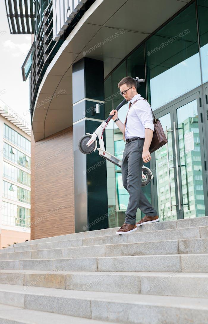 Junger Mann mit Roller verlassen Bürogebäude am Ende des Arbeitstages