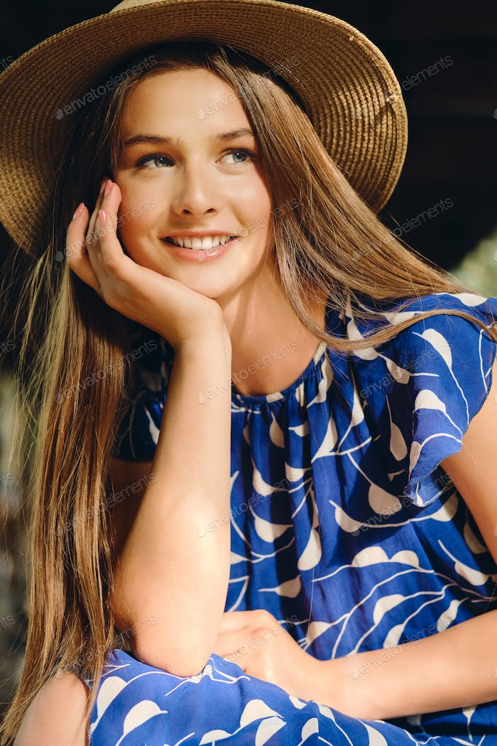 Young attractive brown haired woman in blue dress and hat leaning on hand and happily looking away