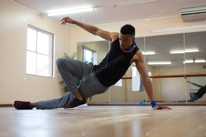 Full length of male dancer practicing on floor