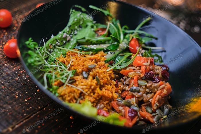 Gekochte vegetarische Schüssel mit Plov auf einem Holztisch